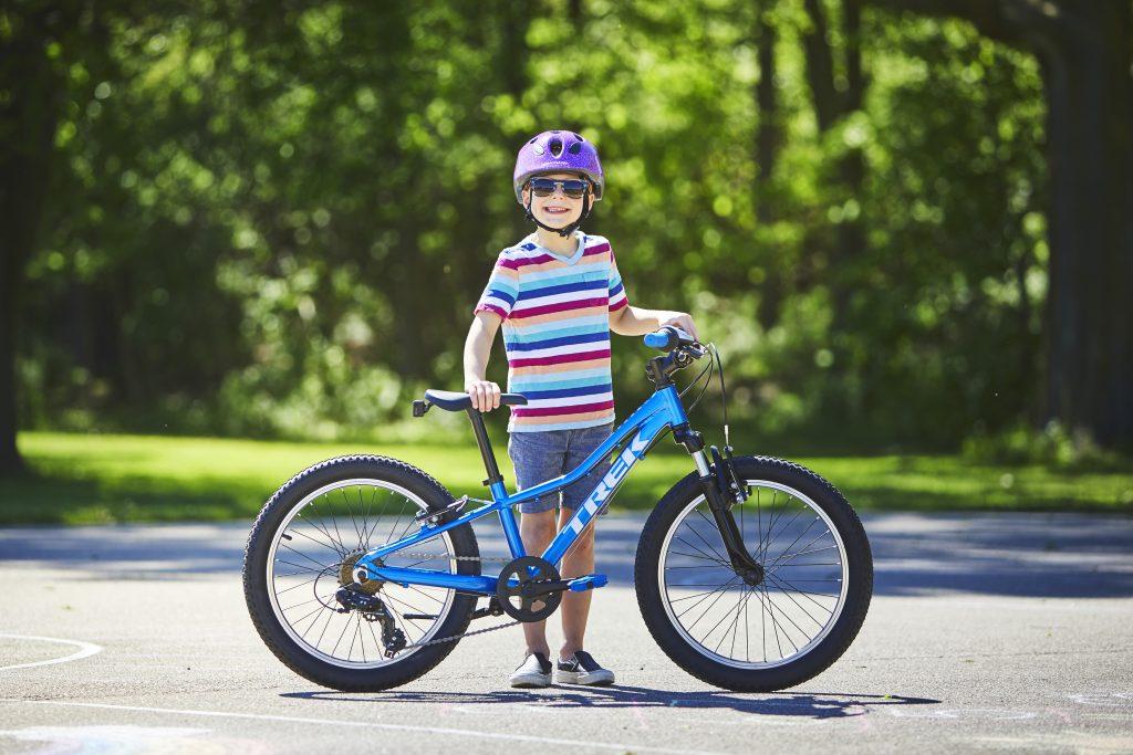 Bike Online Bub in buntgestreiftem T-Shirt genießt die Parkatmosphäre mit seinem blauen Rad von Trek