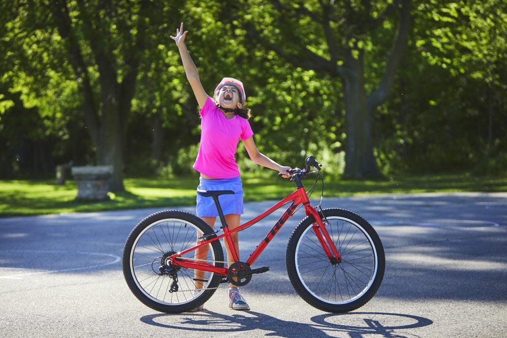 Bike Online Mädchen mit rosa Helm streckt die Hand in die Luft und erfreut sich an der Frühlingslandschaft