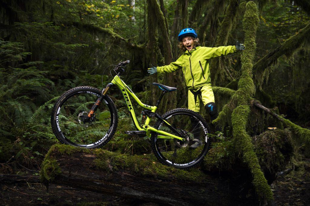 Bike Online Bub in grellgelbem Overall genießt mit seinem Bike den dichten Wald