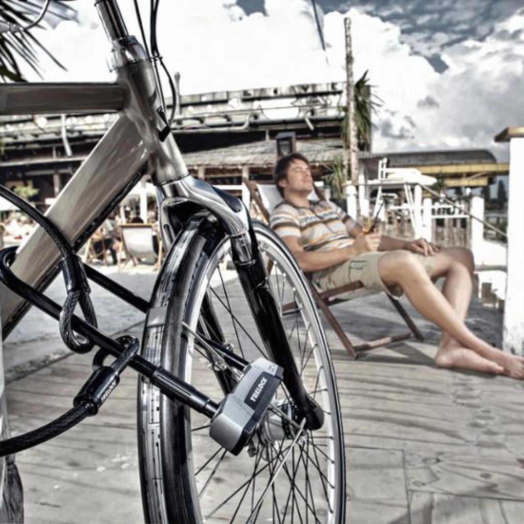 Graues Citybike ist auf einer Strandpromenade mit einem Trelock-Bügelschloss von Bike online gesichert. Im Hintergrund entspannt der männliche Besitzer auf einem Strandsessel mit einem Cocktail