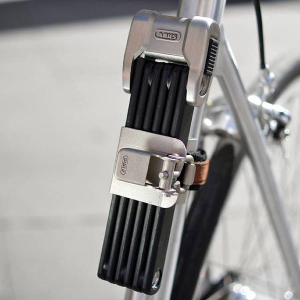 Silbernes Faltschloss der Marke ABUS von Bike Online sichert ein Rennrad