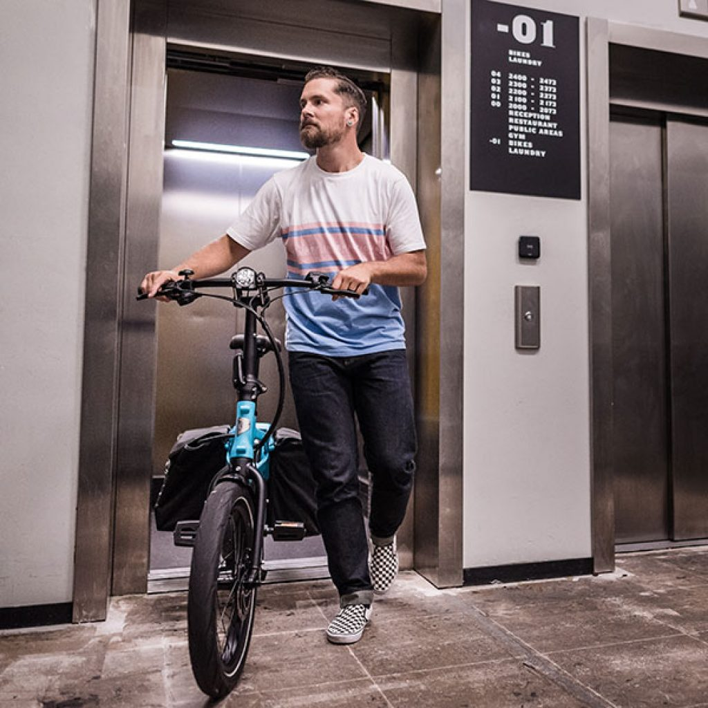 Bärtiger Mann um die 30 mit blauem Tern Lastenrad von Bike Online steigt aus dem Lift aus
