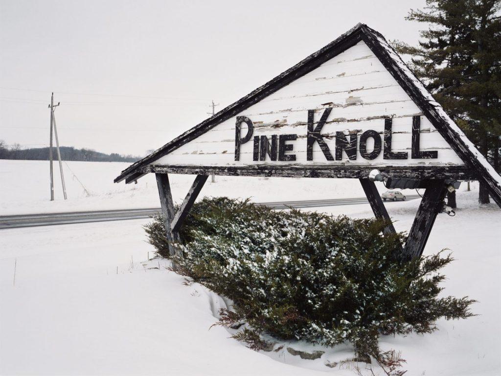"""Winterliche mit Schnee bedeckte Landschaft mit einem Schild mit dem Text """"Pine Knoll"""", das an die amerikanische Bar erinnert, in der der Fahrradproduzent Trek gegründet worden ist"""