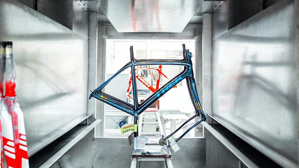 Blauer Fahrradrahmen mit der Aufschrift Trek bei der Produktion
