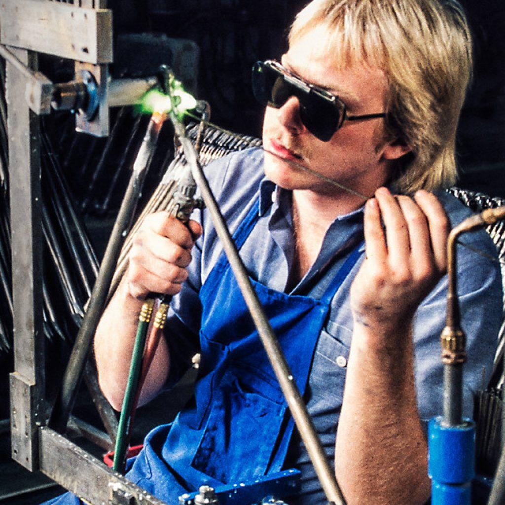 Schweißer mit blonden langen Haaren und Schutzbrille bei der Produktion eines Trek-Fahrrades
